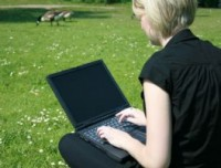 Working on a Computer in the Grass